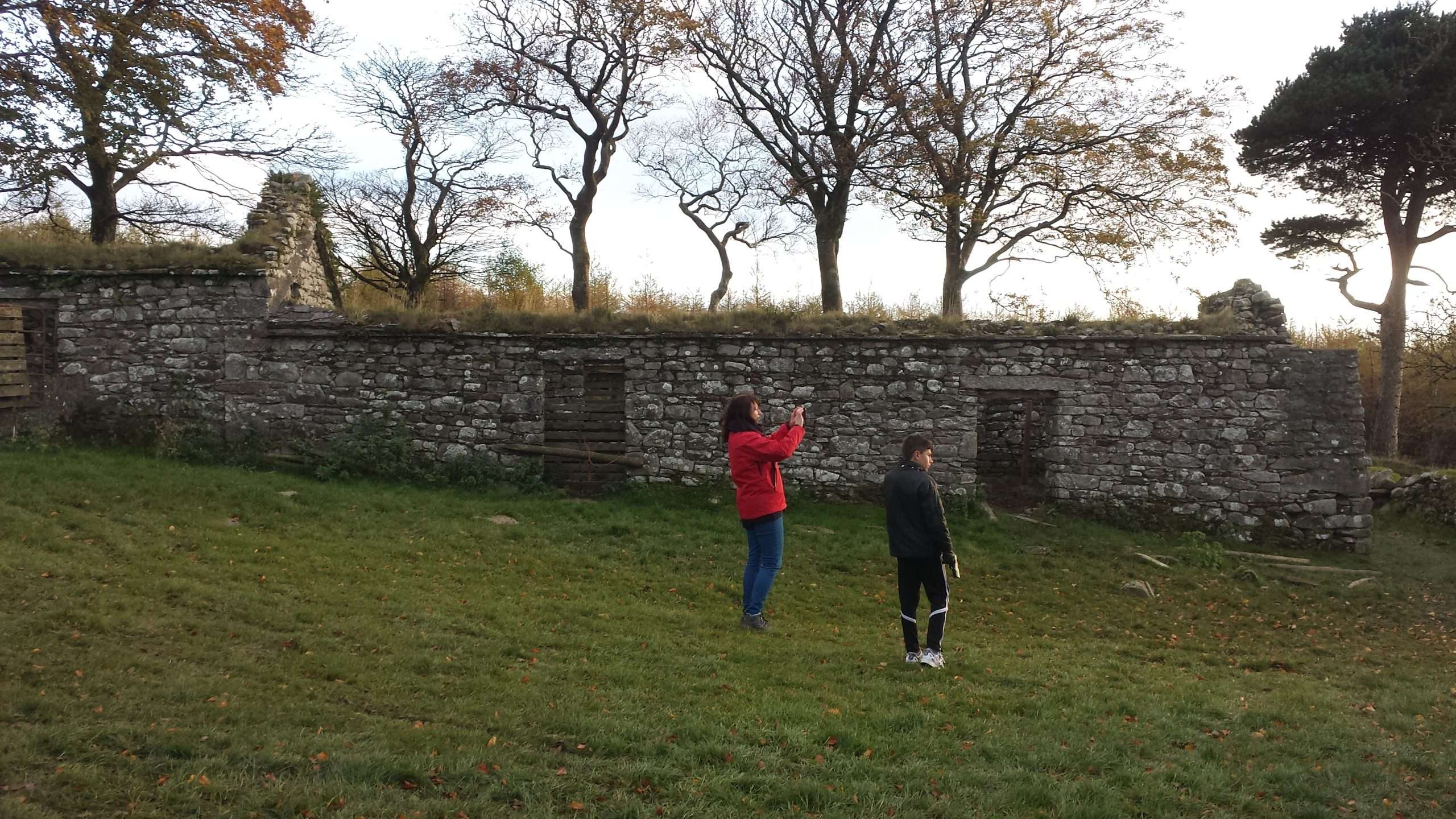 A woman and a boy taking photos at Carrig ruins Wicklow